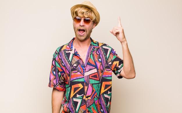 Homem viajante adulto loiro se sentindo um gênio feliz e animado depois de realizar uma ideia, levantando o dedo alegremente, eureka!