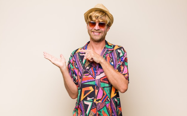 Homem viajante adulto loiro sorrindo alegremente e apontando para copiar o espaço na palma da mão ao lado, mostrando ou anunciando um objeto