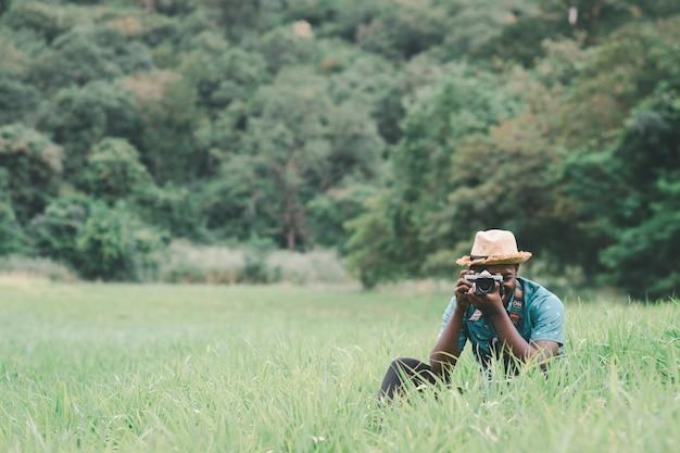 Homem viajante africano tira foto em meio a campo de prados verdes