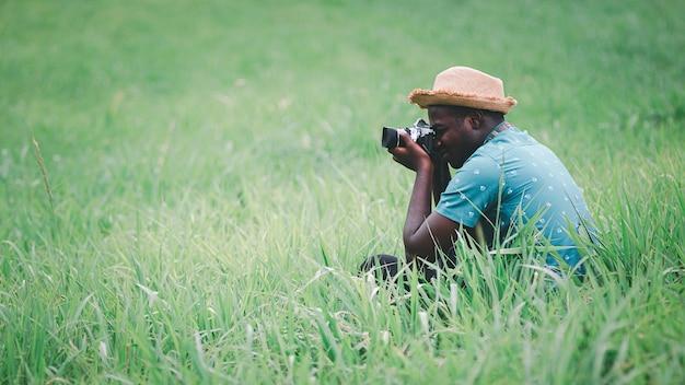 Homem viajante africano tira foto no campo de prados verdes. estilo 16: 9