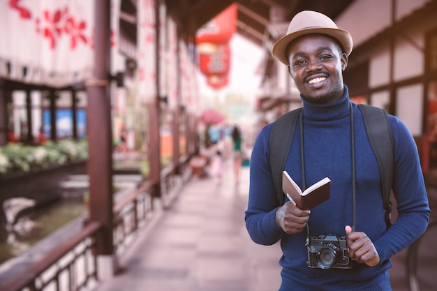 Homem viajante africano viaja pela ásia segurando passaporte e uma câmera vintage