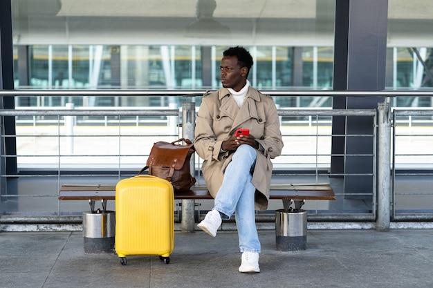 Homem viajante afro-americano com mala sentado no banco no terminal do aeroporto ou estação ferroviária, usando telefone celular, chamando um táxi, esperando o transporte público.