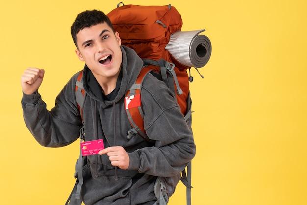 Homem viajante animado com mochila segurando cartão de crédito de vista frontal