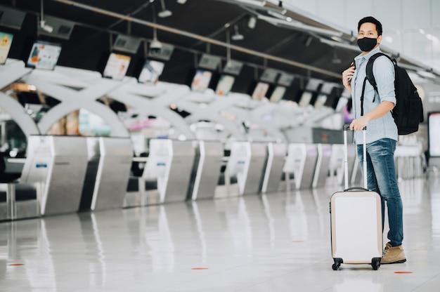 Homem viajante asiático usando máscara para proteção contra coronavírus em pé com a bagagem