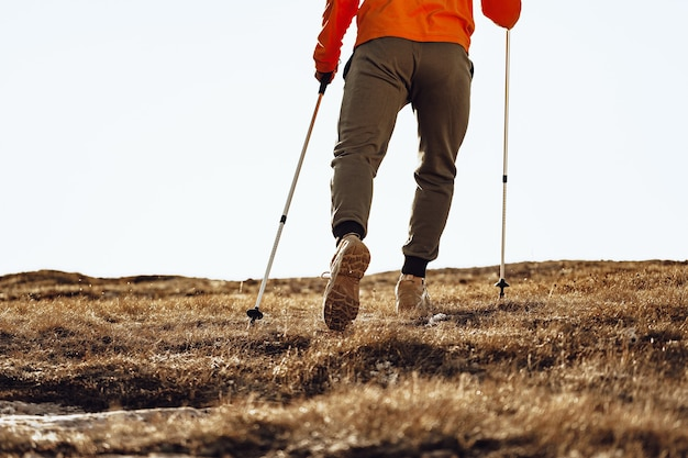Homem viajante com bastões de trekking subindo a montanha