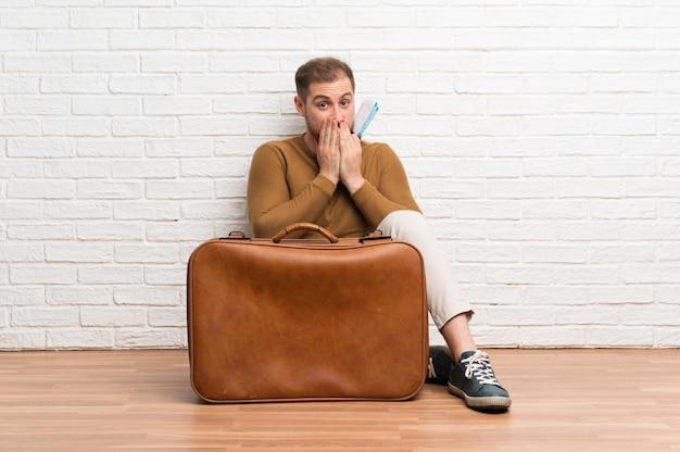 Homem viajante com mala e cartão de embarque com expressão facial de surpresa