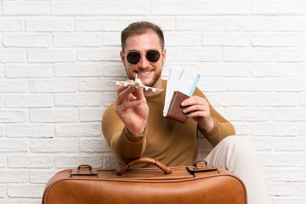 Homem viajante com mala e cartão de embarque e segurando um avião de brinquedo
