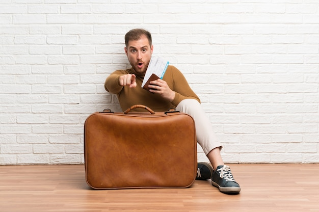 Homem viajante com mala e cartão de embarque surpreso e apontando a frente