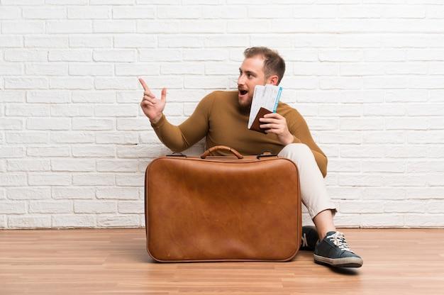 Homem viajante com mala e cartão de embarque surpreso e apontando o dedo para o lado