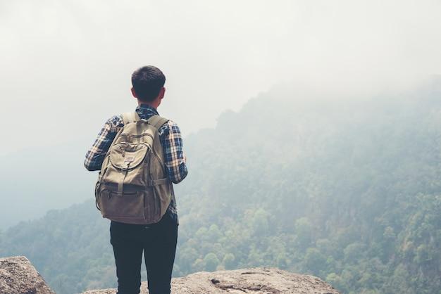 Homem viajante com mochila no topo da montanha. conceito travel lifestyle.