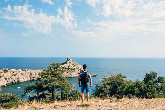 Homem viajante com mochila, olhando para o mar