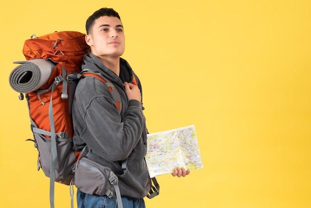 Homem viajante com mochila segurando o mapa e colocando a mão no peito