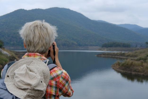 Homem viajante com mochila viagem no lago. mochileiro de turista usar câmera para tirar foto.