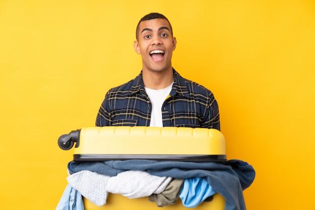 Homem viajante com uma mala cheia de roupas isolado parede amarela com expressão facial de surpresa