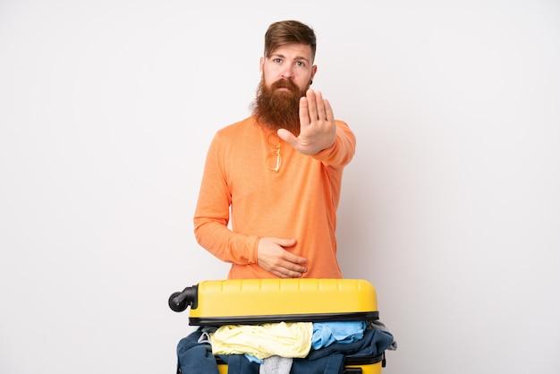 Homem viajante com uma mala cheia de roupas sobre parede branca isolada, fazendo o gesto de parada com a mão