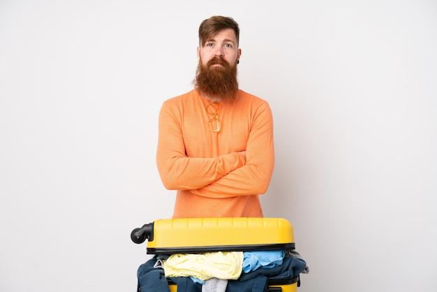 Homem viajante com uma mala cheia de roupas sobre parede branca isolada, mantendo os braços cruzados