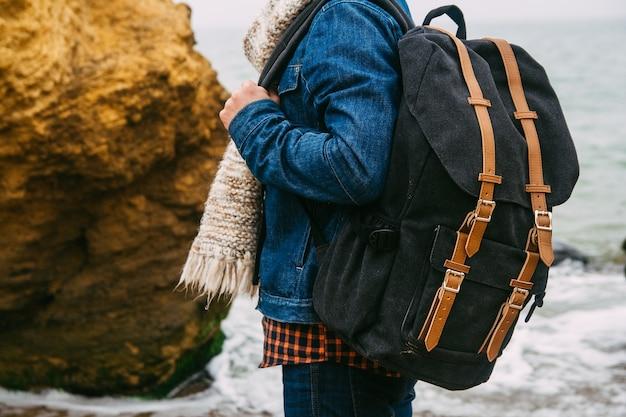 Homem viajante com uma mochila em uma praia arenosa em um fundo de mar com pedras