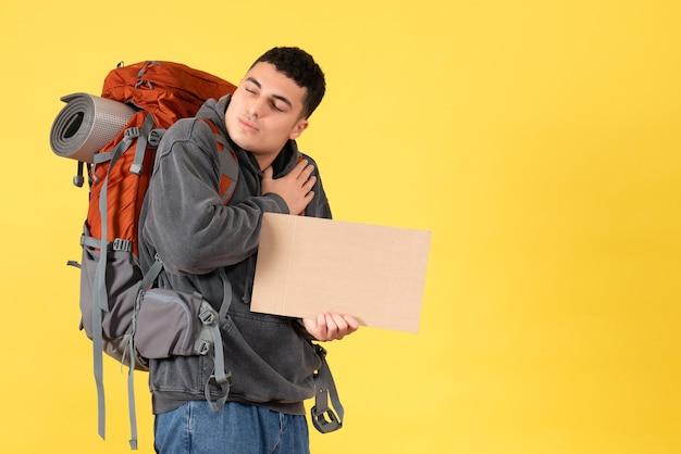 Homem viajante com uma mochila segurando um papelão e colocando a mão no peito