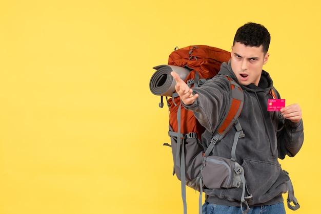 Homem viajante de vista frontal com mochila vermelha segurando o cartão de crédito estendendo a mão