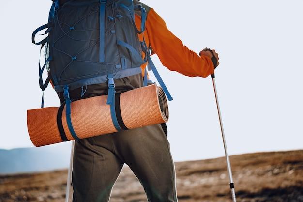 Homem viajante em roupas esportivas com bastões de trekking subindo a montanha