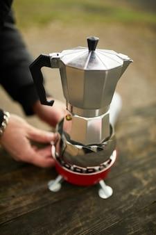 Homem viajante fazendo café para acampamento ao ar livre com cafeteira de gêiser de metal em um fogão a gás