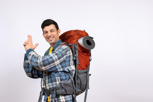 Homem viajante feliz de vista frontal com mochila fazendo arma de dedo