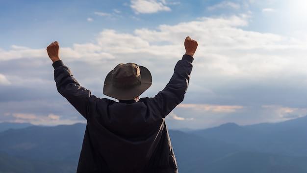 Homem viajante feliz em pé e levantar as mãos para mostrar sucesso no topo da montanha