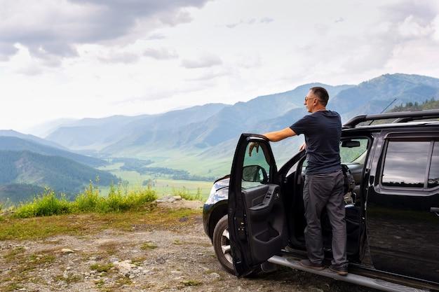 Homem viajante feliz em pé em seu carro no topo das montanhas.