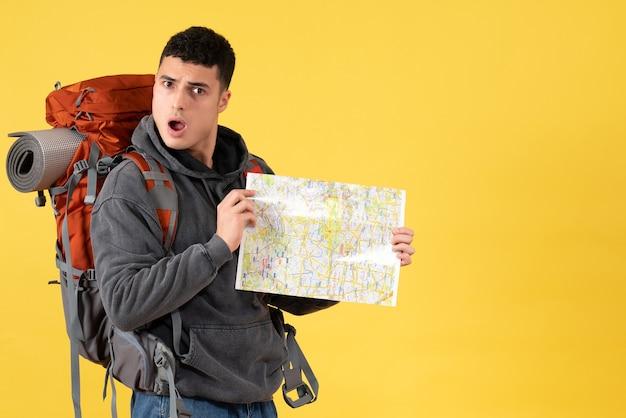 Homem viajante intrigado de frente com uma mochila segurando o mapa