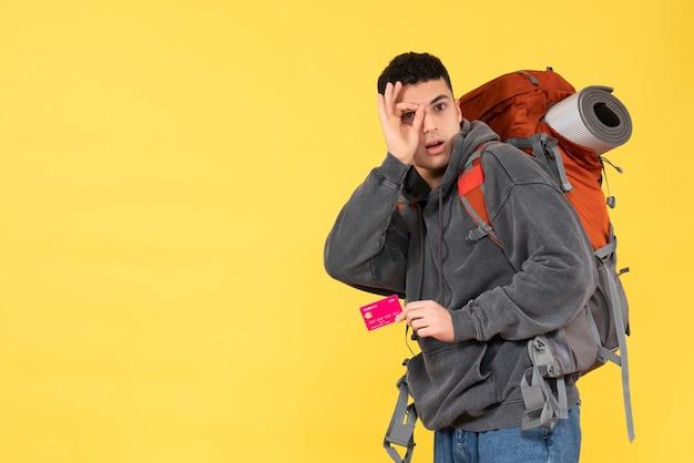 Homem viajante legal com uma mochila vermelha segurando um cartão de desconto de vista frontal