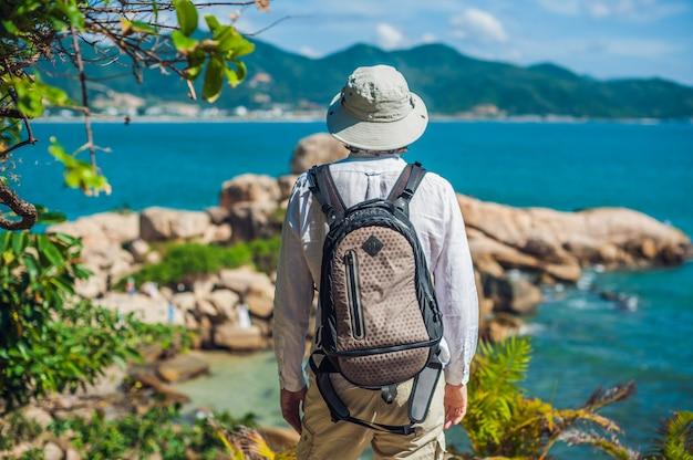 Homem viajante olhar para capa de hon chong, pedra de jardim, destinos turísticos populares em nha trang. vietnã
