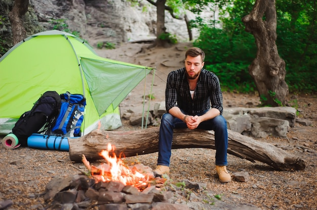 Homem viajante relaxante, olhando para o fogo e sonhando na barraca de acampamento ao ar livre na natureza