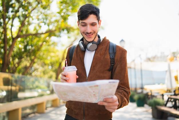Homem viajante segurando um mapa e procurando instruções.