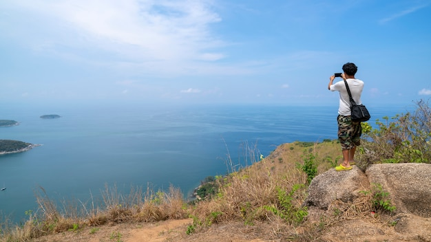 Homem viajante sozinho tira uma foto de uma bela paisagem