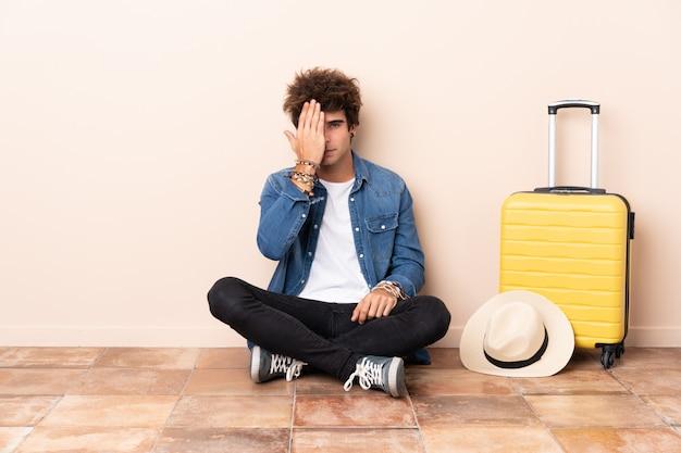 Homem viajante sua mala sentado no chão, cobrindo um olho com a mão