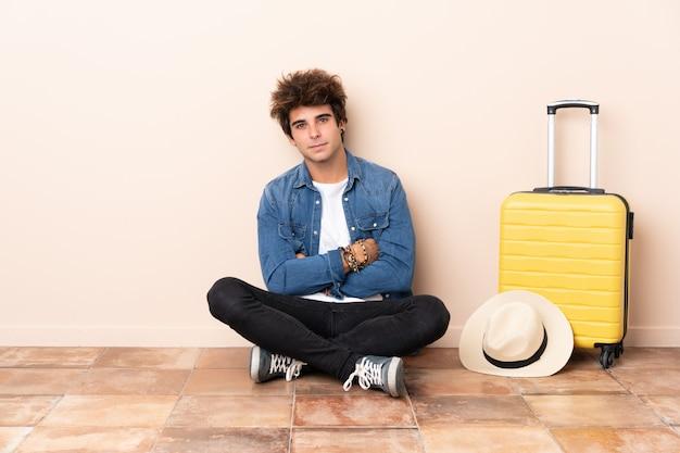 Homem viajante sua mala sentado no chão, mantendo os braços cruzados