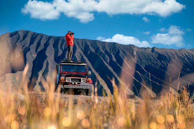 Homem viajante tirar uma foto em um carro off-road vintage com montanha bromo