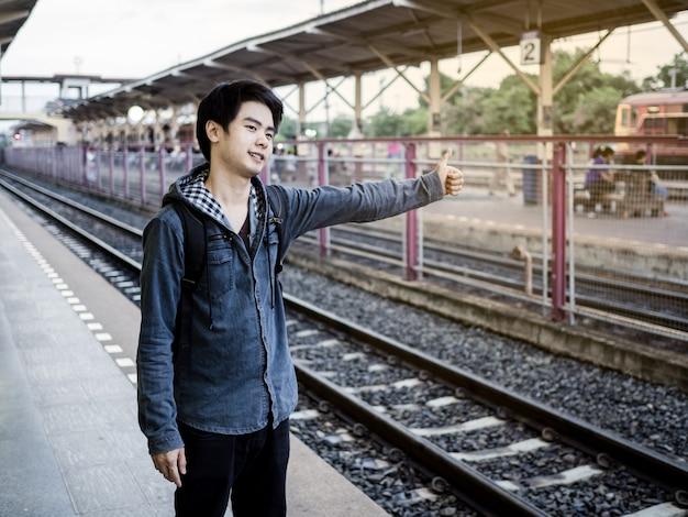 Homem viajar está esperando trem na plataforma da estação ferroviária e thump up