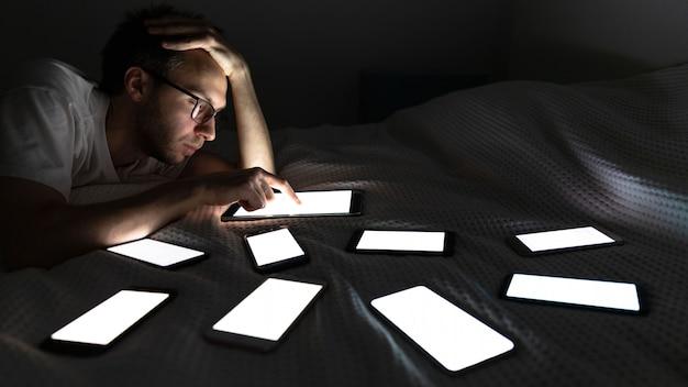 Homem viciado em gadget usando tablet tarde da noite, conversando nas redes sociais, deitado na cama ao redor do conjunto de telefone ligado