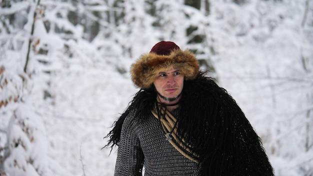 Homem viking indo na floresta de inverno.