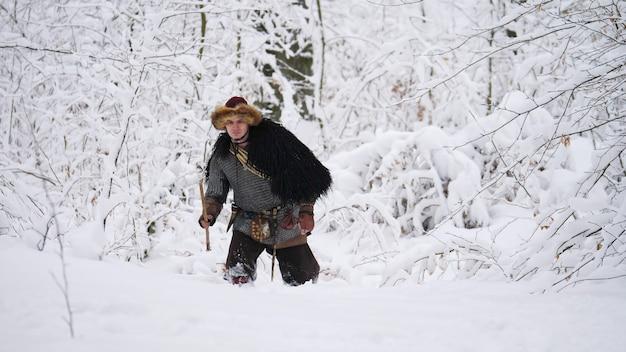 Homem viking indo para a floresta de inverno