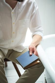 Homem vintage em roupas brilhantes mãos segurar um livro fechado