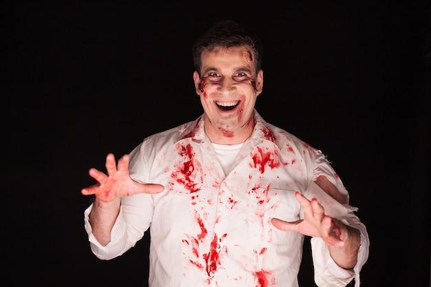 Homem violento e assustador com sangue em seu corpo, sobre fundo preto.