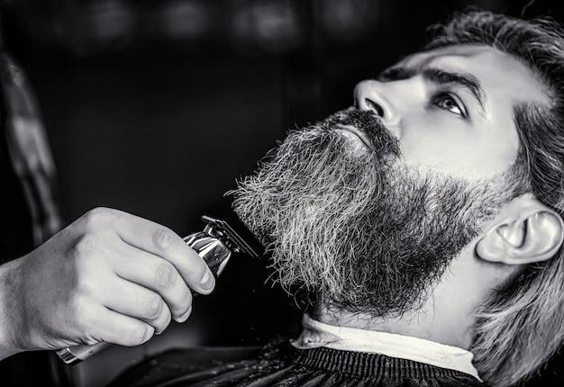 Homem visitando cabeleireiro na barbearia. o barbeiro trabalha com um cortador de barba. mãos de um cabeleireiro com um cortador de barba, closeup