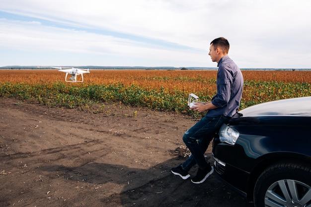 Homem voando em um drone no campo amarelo