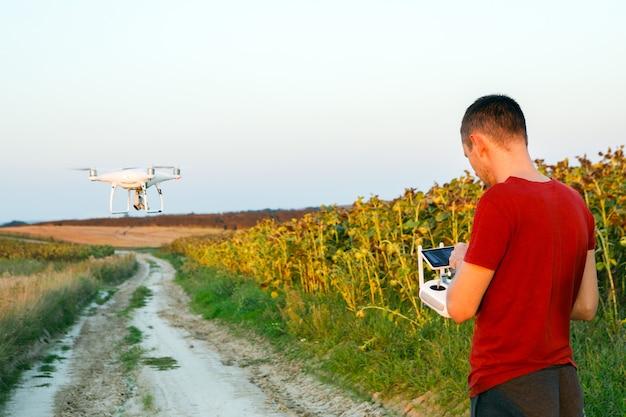 Homem voando um drone no campo verde. jovem navegando em um drone voador