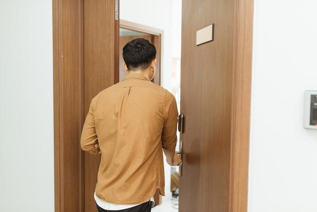 Homem voltando do trabalho e abrindo a porta do apartamento