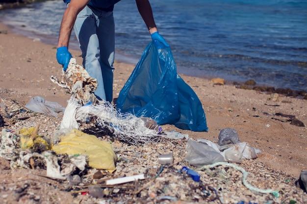 Homem voluntário com saco grande para coleta de lixo na praia. conceito de poluição ambiental
