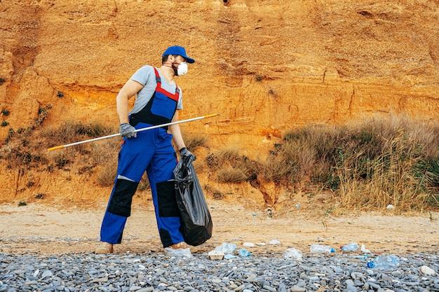 Homem voluntário uniformizado recolhendo lixo na praia com um extensor de alcance