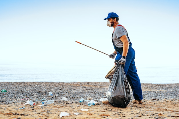 Homem voluntário uniformizado, recolhendo lixo na praia com um extensor de alcance